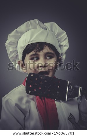 boy dressed as a cook with kitchen utensils - stock photo