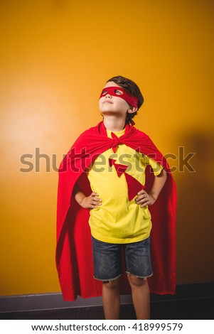 Boy dressed as a superhero on yellow background