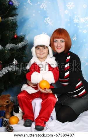 boy dressed as Santa Claus around Christmas tree with my mother