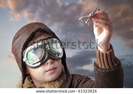 Boy dressed up in pilot?s outfit, jacket, hat and glasses.
