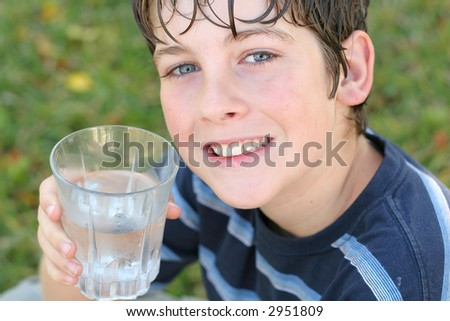 boy drinking a glass of water smile - stock photo
