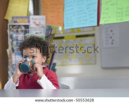 Boy drinking from cup in classroom - stock photo