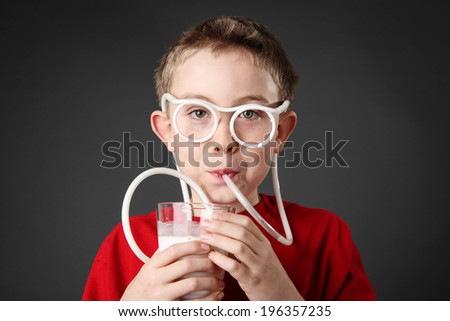Boy drinking milk through a silly straw - stock photo