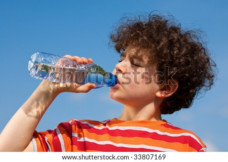Boy drinking water against blue sky - stock photo