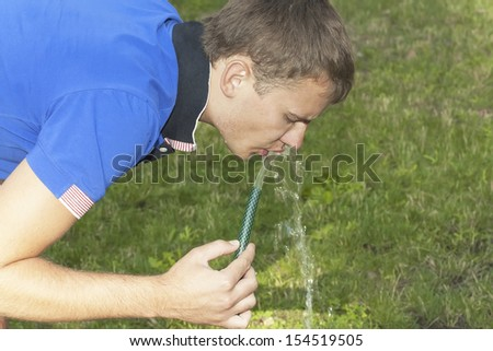 boy drinks water from a hose on a background of green grass