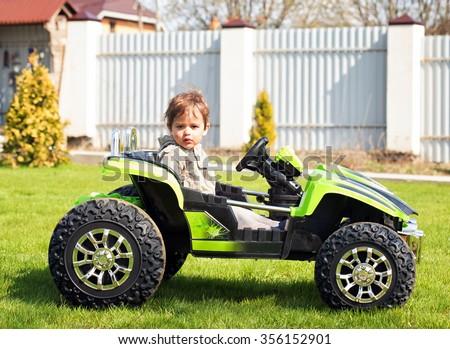 Boy drive electric mini car in the garden - stock photo