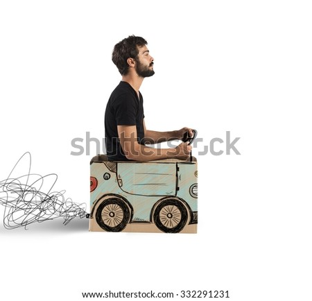 Boy driving a fake designed cardboard car - stock photo