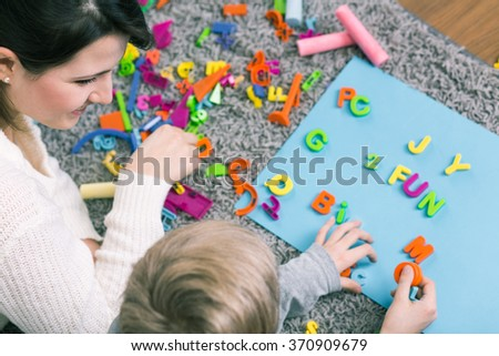 Boy during session with speech therapist learning letters - stock photo