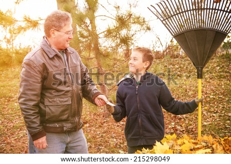 Boy earning money from raking leaves - stock photo