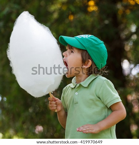 Boy eat candyfloss at the park - stock photo