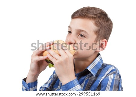 Boy eating a huge burger fresh and smiling