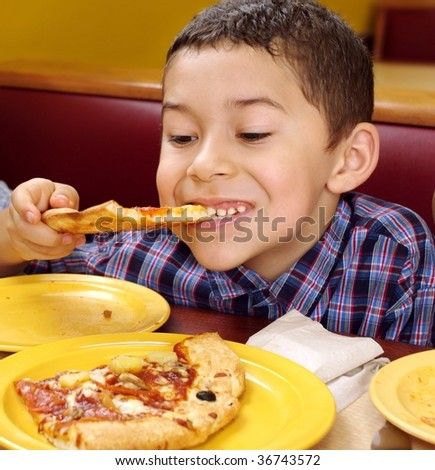 boy eating a slice of pizza, seven years old - stock photo
