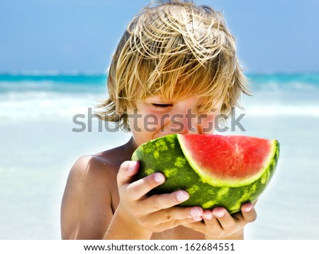 boy eating a slice of watermelon on the beach - stock photo