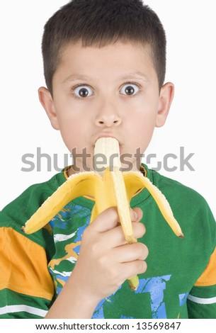 Boy eating banana isolated on white background - stock photo