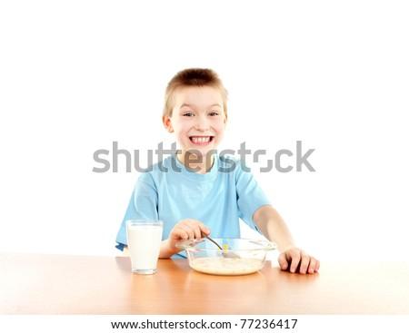 boy eating corn flakes isolated on the white - stock photo
