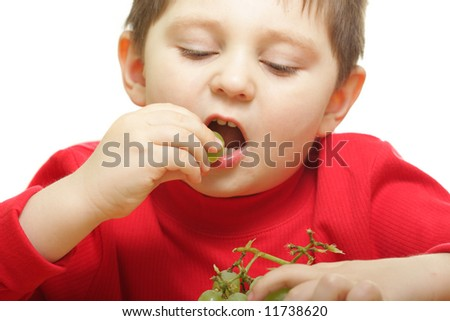 Boy eating grapes isolated over white