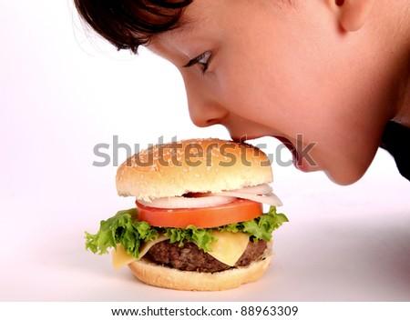 boy eating hamburger. close up - stock photo