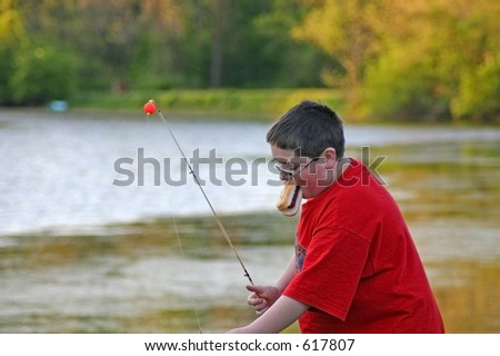 Boy eating hotdog while trying to fish - stock photo