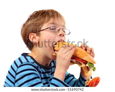 boy eating large sandwich on white background - stock photo