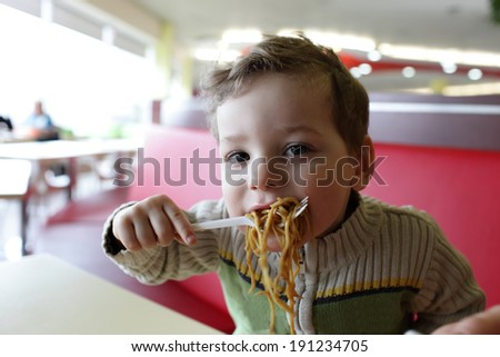 Boy eating noodles in the asian restaurant - stock photo