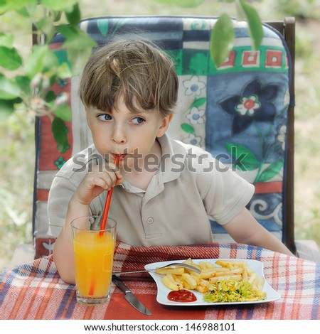 boy eating outdoors - French fries with ketchup - stock photo