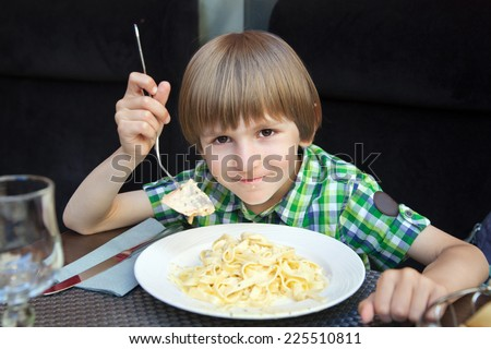 boy eats pasta with salmon in a cafe