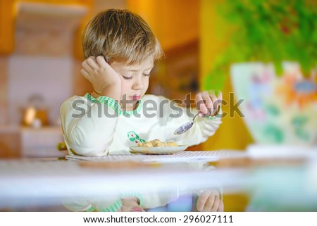 boy eats with a spoon at the table thinking - stock photo