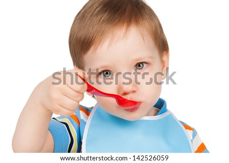 Boy eats with a spoon, isolated on white - stock photo