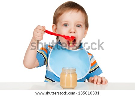 Boy eats with a spoon puree - stock photo