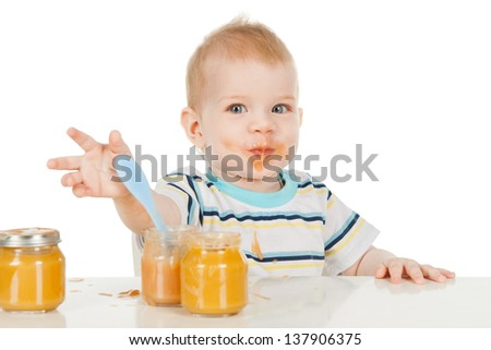 Boy eats with a spoon puree, isolated on white - stock photo