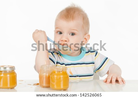 Boy eats with a spoon puree, on a gray background - stock photo