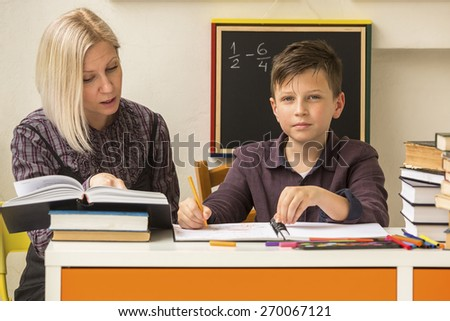 Boy engaged in the lessons at home with his mum. - stock photo