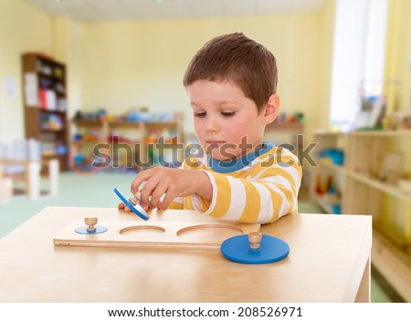 Boy engaged in the Montessori classroom.kindergarten, the concept of childhood and joy, teens - stock photo