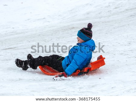 Boy enjoy a sleigh ride. Child sledding. Children play outdoors in snow. Kids sled in Alps mountains in winter. Outdoor fun for family Christmas vacation. - stock photo