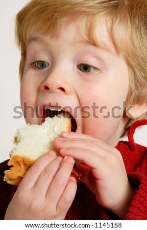 Boy enjoying a peanut butter and jelly sandwich - stock photo