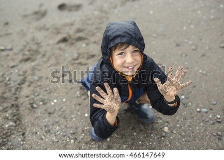 boy enjoying the rain and having fun outside on the beach  a gray rainy