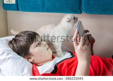 Boy enjoys the tablet on the train, kitten sitting near  - stock photo