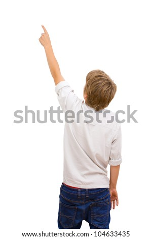 Boy facing backwards and pointing with finger at copy space.Isolated on white.