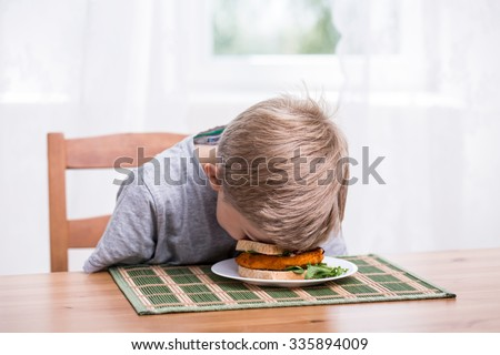Boy falling asleep and landing face in food - stock photo