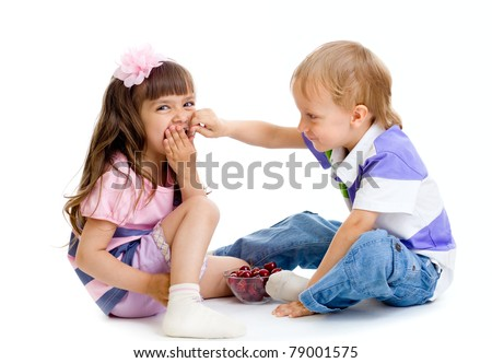 boy feeds little girl with cherry berries in studio isolated - stock photo