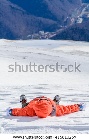 Boy fell down over fresh snow. Happy boy laying on snow on his back. Cute little kid boy in colorful winter clothes laying down on snow, hand gloves, winter fashion. - stock photo