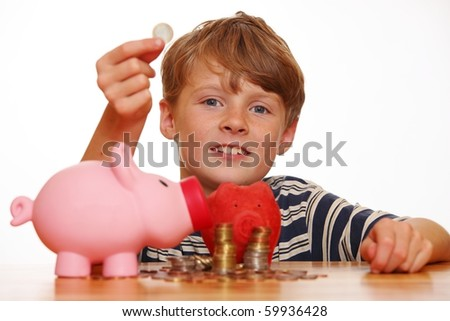 Boy fills his piggybank - stock photo