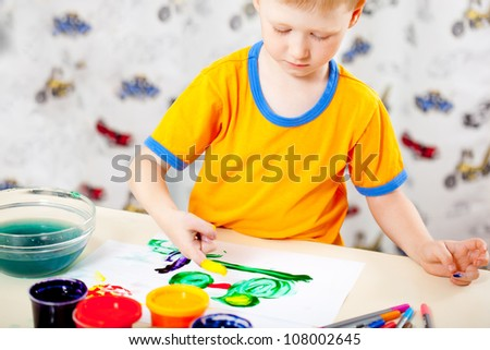 Boy finger paints on paper at his playroom - stock photo