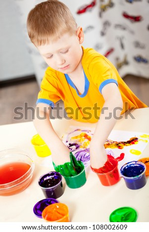 Boy finger paints on paper at his room, vertical photo - stock photo