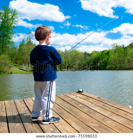 Boy fishing from dock on lake. - stock photo