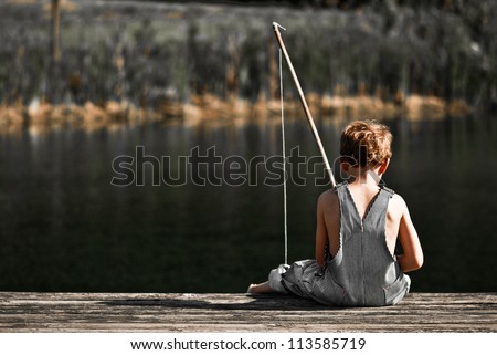 Boy fishing in overalls from a dock on a lake or pond with text space to the left. - stock photo