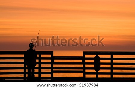 Boy fishing off a pier during sunrise - stock photo