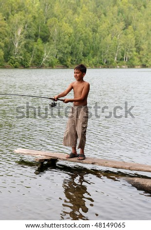 boy fishing with spinning on stage in lake - stock photo