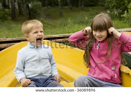 boy five years old shouting and girl cloher ears - stock photo