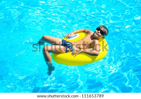 Boy floating on an inflatable circle in the pool. A child in the pool - stock photo